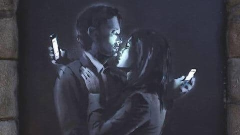 Banksy art couple using smartphones and ignoring each other