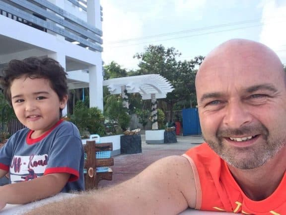 A picture showing the naked expat website owner Andrew with his son. Sitting outside near the beach.