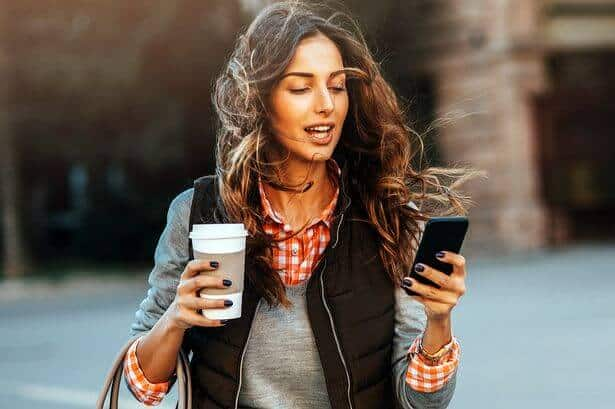 Image of a busy woman walking whilst holding a coffee in one hand and smartphone in the other.