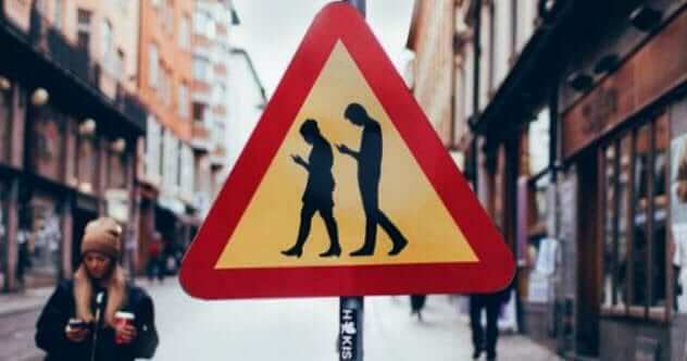 A humorous road traffic warning sign showing people looking down at their phones and not looking where they are going